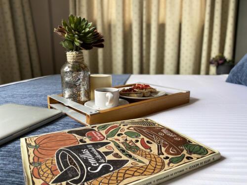 comida, libro y laptop sobre la cama