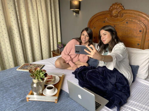 dos mujeres tomando una selfie sobre la cama