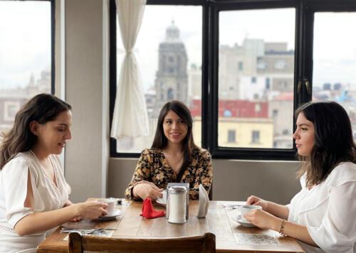 tres mujeres en una mesa tomando cafe